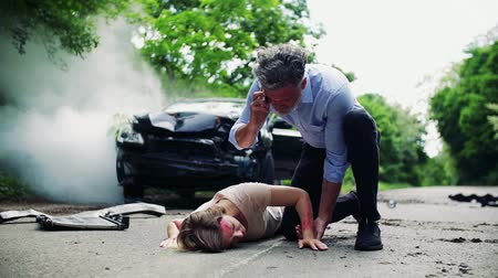 primeiro socorro : A man with telephone helping a young woman lying on the road after a car accident.