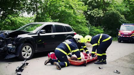 samochód : Firefighters putting an injured woman into a plastic stretcher after a car accident.