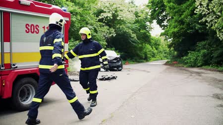 acidente : Two firefighters getting ready to extinguish a burning car after an accident. Stock Footage