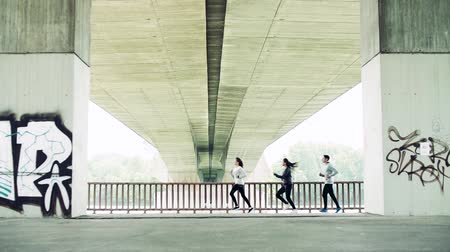 перила : Young athlete friends running under the bridge in the city.