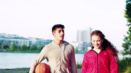 Словакия : Young sporty couple with basket ball walking in the city, talking.