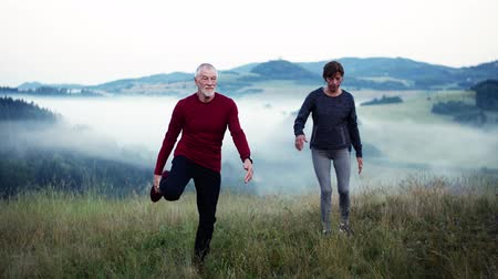 cross training : Senior couple runners stretching on meadow outdoor in foggy morning in nature.