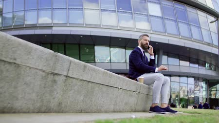 kívül : Hipster businessman with coffee and smartphone sitting on a bench on the street.