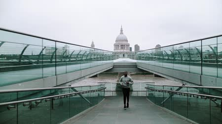 londýn : Young sporty black man runner with smart phone running on the bridge in London. Dostupné videozáznamy