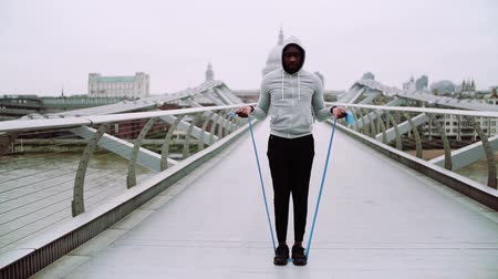 gumka : Young active black sportsman exercising with elastic rubber bands in London.