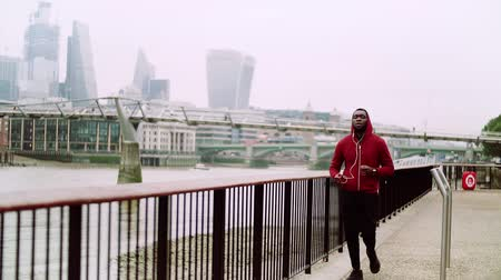 прослушивание : Young sporty black man runner running on the bridge outside in a London city. Стоковые видеозаписи