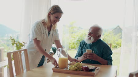 tray : Health visitor and a senior man during home visit. Stock Footage