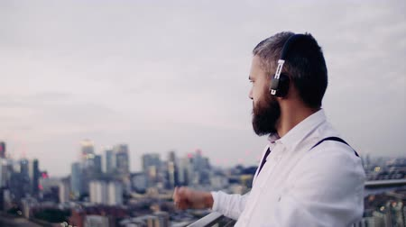 ing és nyakkendő : A cheerful businessman with headphones standing against London view panorama. Stock mozgókép