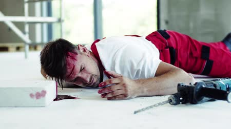 bleeding : A man worker with bleeding wound on head lying on the floor after accident.