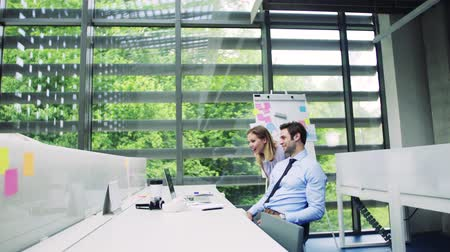kolsuz : Two young business people in the modern office working together.