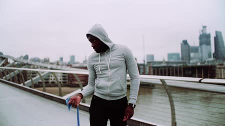 resistência : Young active black sportsman exercising with elastic rubber bands in London.