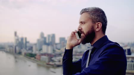 воротник : A portrait of businessman with smartphone standing against London view panorama. Стоковые видеозаписи
