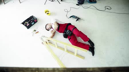 vyrovnání : Top view of an accident of a man worker at the construction site. Dostupné videozáznamy