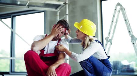 čelo : A woman helping man worker after an accident at the construction site.