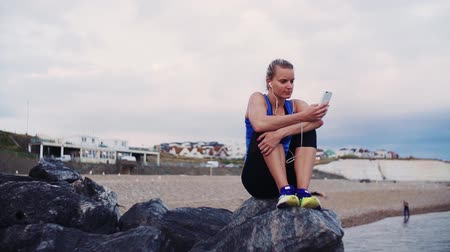 бегун трусцой : Young sporty woman runner sitting on rocks on the beach outside, listening to music.
