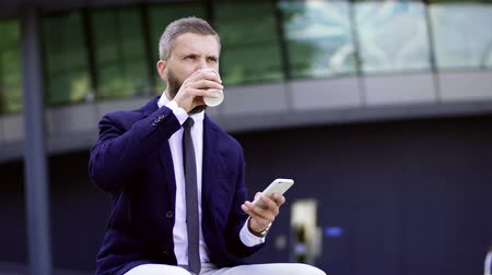 воротник : Hipster businessman with coffee and smartphone sitting on a bench on the street.