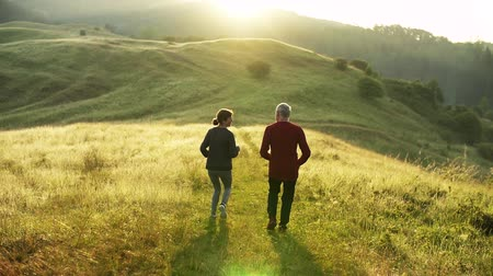 cross country : Rear view of senior sporty couple running on meadow in nature at sunrise. Stock Footage