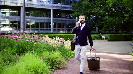 воротник : Hipster businessman with smartphone and suitcase walking in park in London.