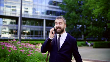 ing és nyakkendő : Hipster businessman with smartphone walking in park in London. Stock mozgókép