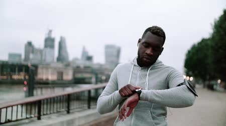 londyn : Young sporty black man runner with smart watch walking on the bridge in a city. Wideo
