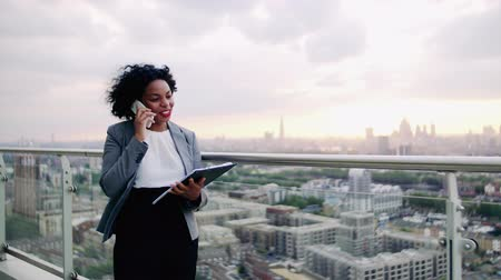 reszelő : A portrait of a businesswoman standing on a terrace, making a phone call. Stock mozgókép
