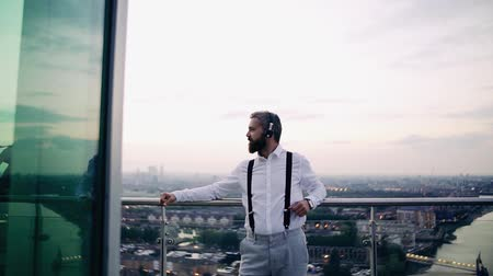 bretels : A cheerful businessman with headphones standing against London view panorama. Stockvideo