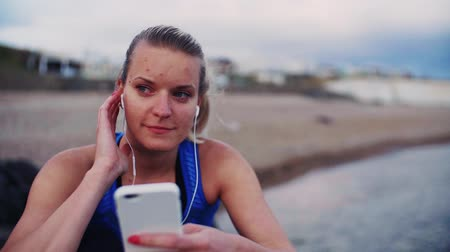 recreational pursuit : Young sporty woman runner sitting on rocks on the beach outside, using smartphone. Stock Footage