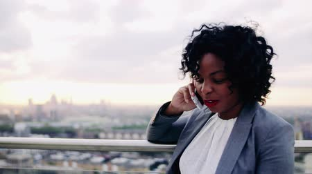 содержание : A portrait of a businesswoman standing on a terrace, making a phone call. Стоковые видеозаписи