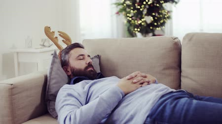 deer : A man with reindeer headband lying on a sofa at Christmas time, sleeping.