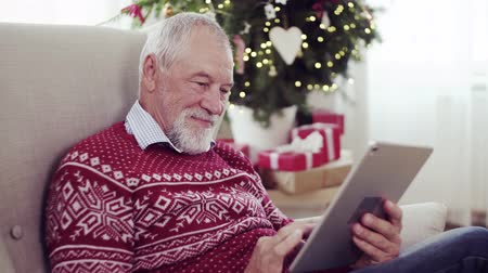 christmas tree with lights : A portrait of senior man with tablet sitting on armchair at home at Christmas time.