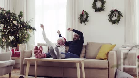 father christmas : Senior father and adult son sitting on a sofa at Christmas time, having fun. Stock Footage