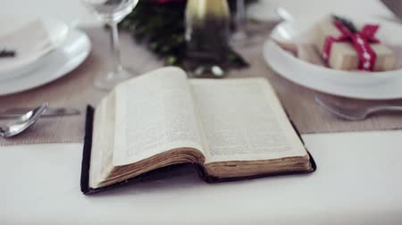 jesus born : Holy bible book on a table set for a dinner at home at Christmas time.