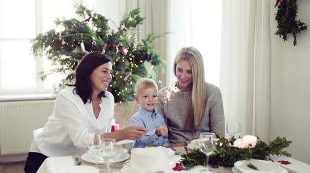 святки : A small boy with mother and grandmother holding sparkles at Christmas time.