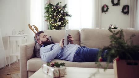 celebration : A man with reindeer headband lying on a sofa at Christmas time, using tablet. Wideo