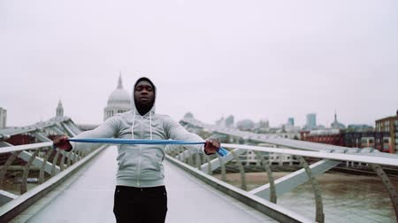 direnç : Young active black sportsman exercising with elastic rubber bands in London.