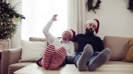 в отставке : Senior father and adult son sitting on a sofa at Christmas time, having fun. Стоковые видеозаписи