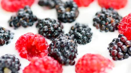 ягоды : White yogurt with fresh raspberries and blackberries. Short clip with zoom in effect.