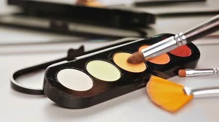 kurulamak : Makeup brush moving over multicolor eye shadows palette
