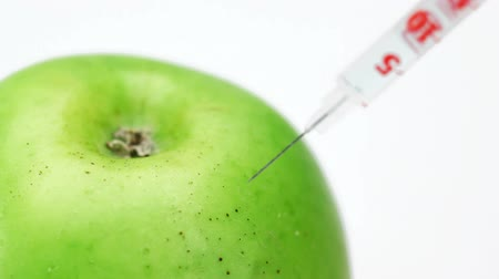 укол : GMO apple injection with syringe on the white background