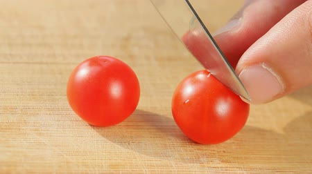 keser : Cherry tomatoes cutting with kitchen knife on wooden board Stok Video