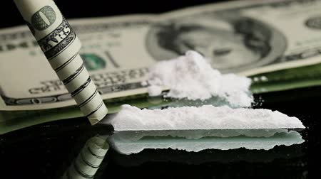 kola : Cocaine snorted on a mirror through rolled 100 dollar bank note, close up view Stok Video