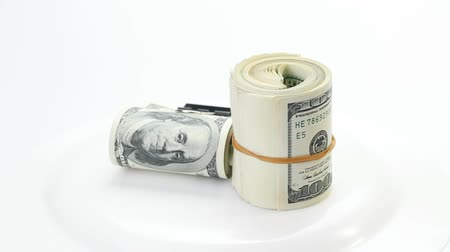 value clips : Bundle of many 100 dollar bank notes rolled up and fasten with paper clip rotating on a white background