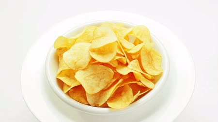 brambory : Potato chips heap rotating on a white plate, closeup view Dostupné videozáznamy