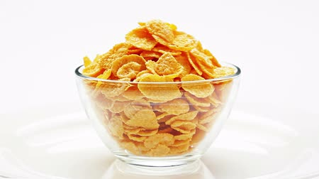 miska : Corn flakes heap in a glass bowl rotating over white, loop ready
