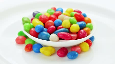 colorful candy : Multicolor bonbon sweets (ball candies) rotating on white plate, loop ready Stock Footage