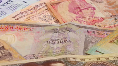 threadbare : Different asian currency bank notes rotating and panning business background