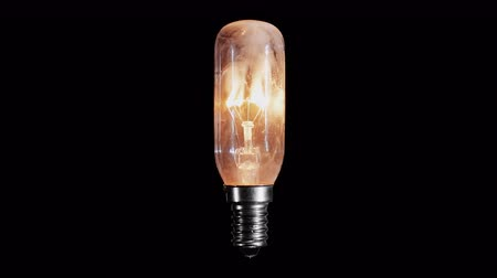 yanmak : Light bulb lamp flickers and burns out with flame over black background Stok Video