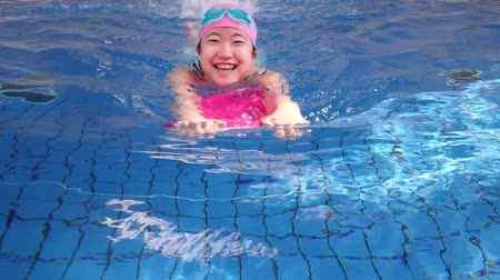 Japanese girl swimming with kickboard in the swimming pool