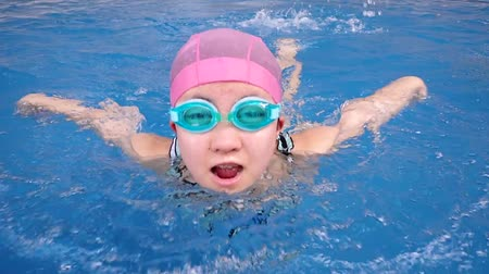 Japanese girl swimming the butterfly in the swimming pool