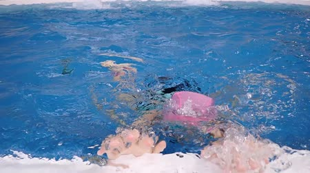 Japanese girl swimming the breaststroke in the swimming pool